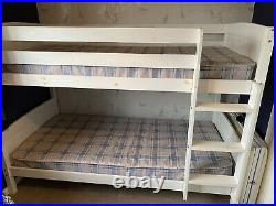 White wooden bunk beds with mattresses